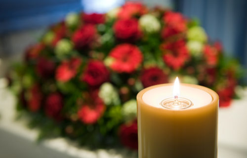 A burning candle with a white coffin and a flower arrangement on the background in a mortuary